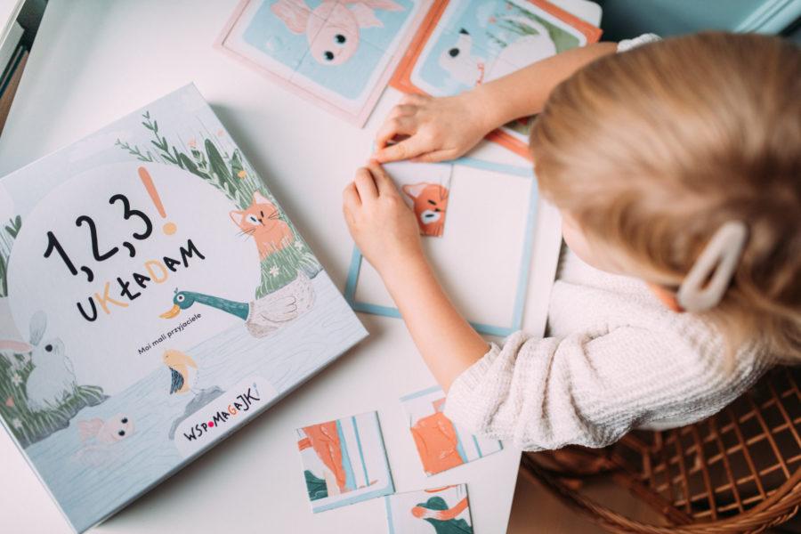 Dziewczynka układa układankę Wspomagajki