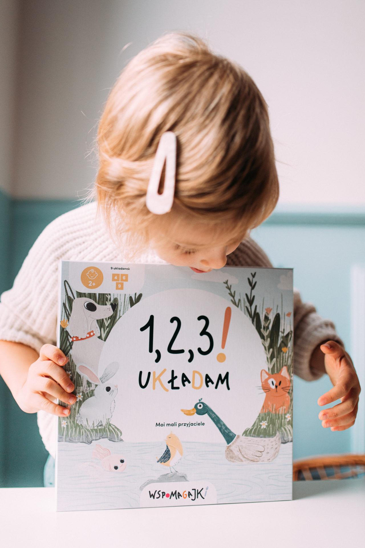Dziewczynka trzyma układankę Wspomagajki