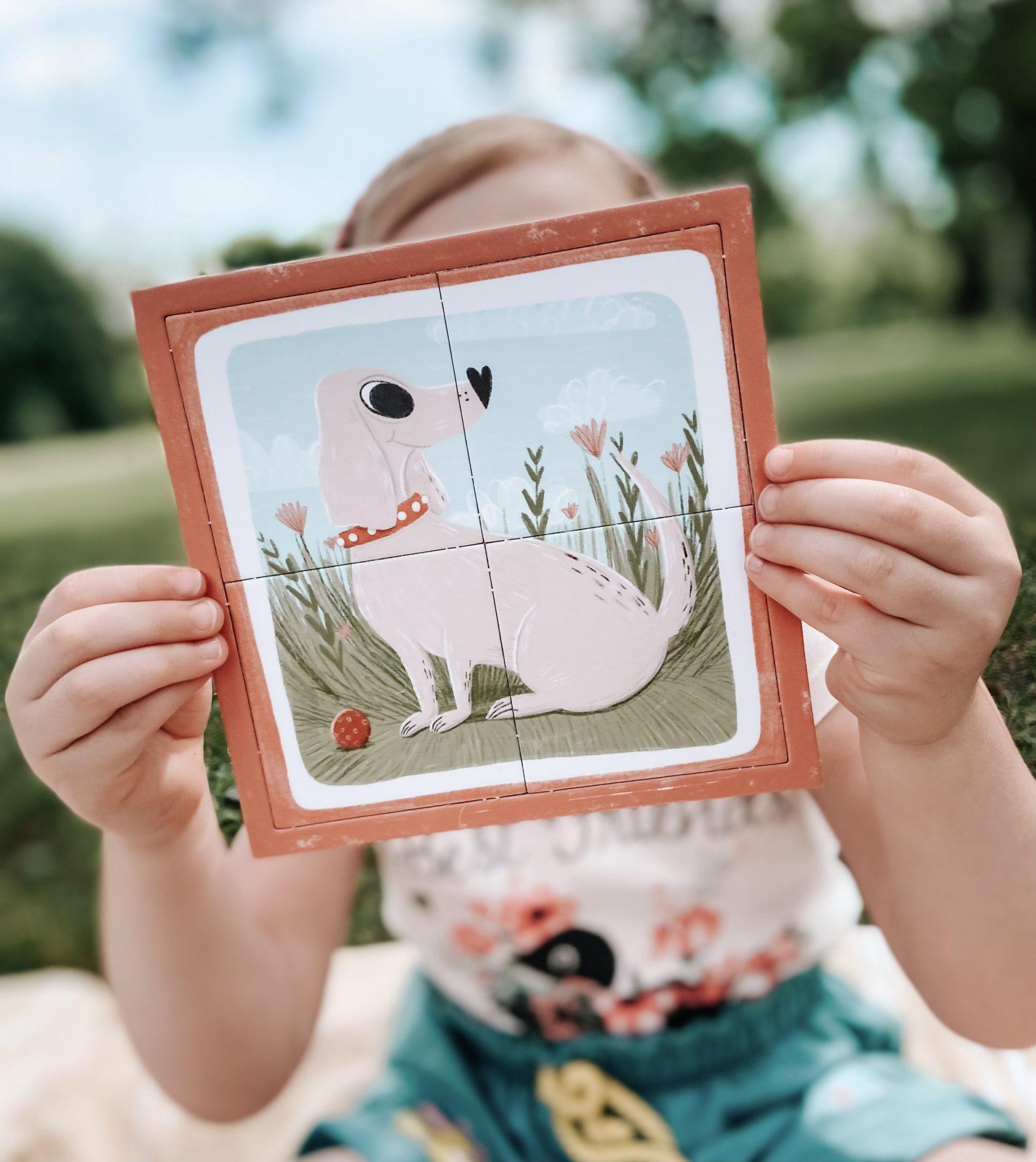 Dziewczynka układa układankę z pieskiem