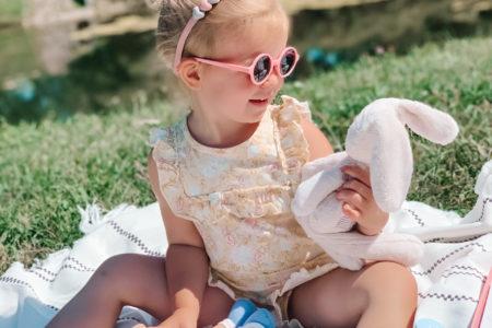 dziewczynka bawi się misiem i lalą